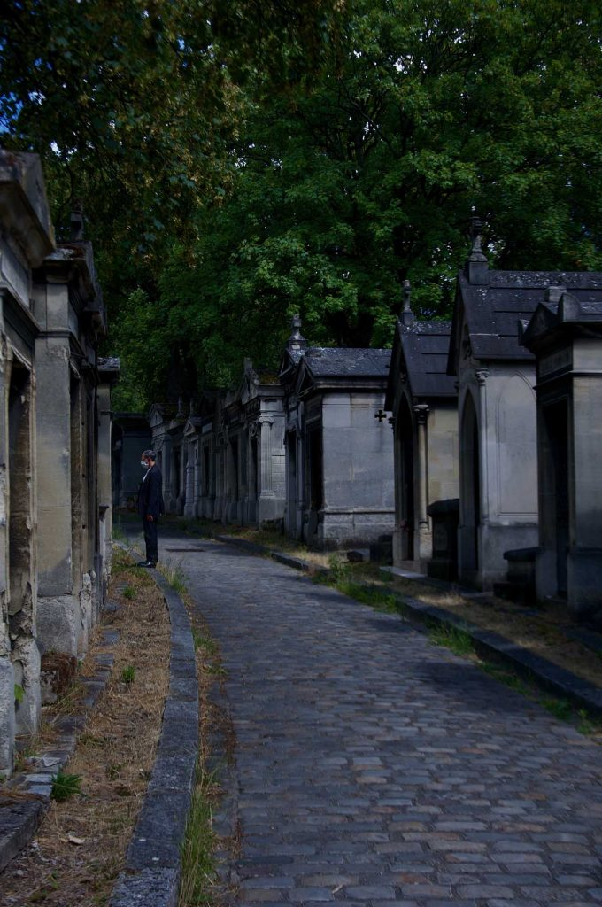 Ashley Hyde Harrison - Stone path with rows of stone mausoleums on each side and man standing to the left