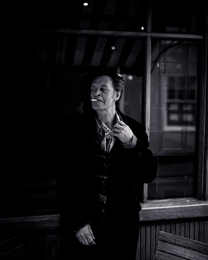 Charlie Sargeant - Black and white image of a man smoking a cigarette and looking away
