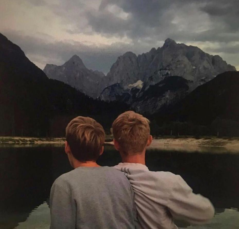 Eliza Shippam - Two men sitting shoulder to shoulder looking at mountains