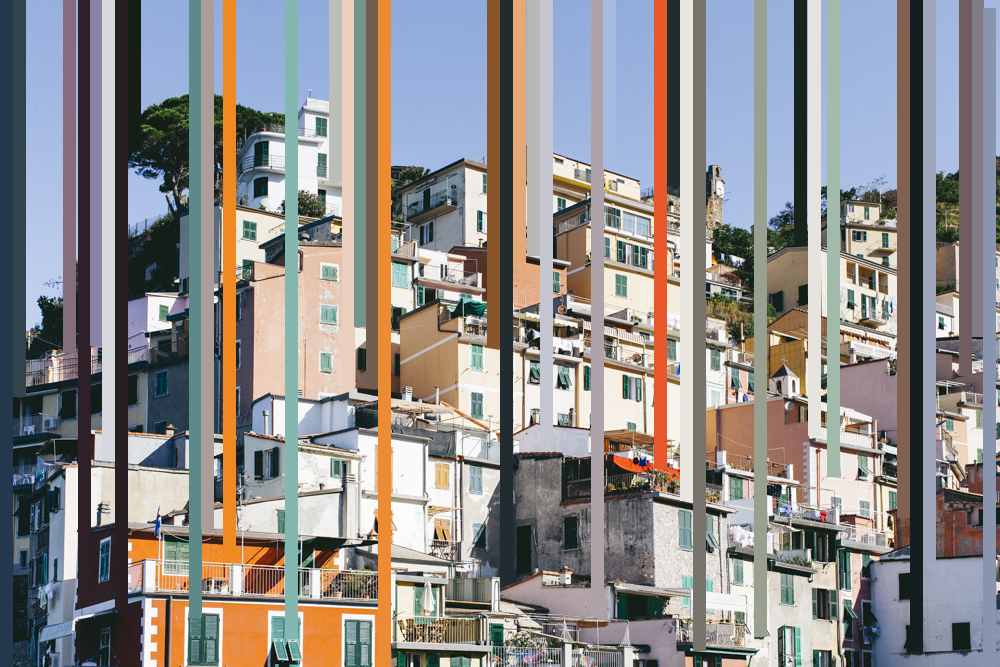 Emma Abram - A hillside covered in sunlit buildings against a blue sky with strips of vertical colour across the buildings