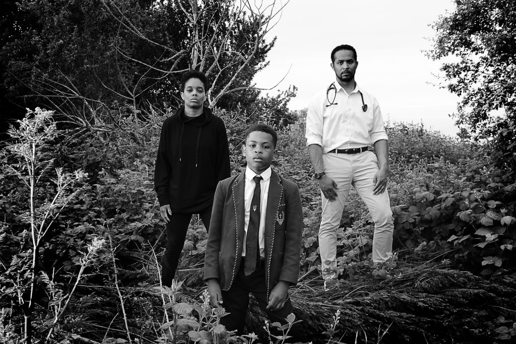 Ivana Peat - Black and white photo of a young black boy, black teenager and black man standing amongst shrubbery and looking at the camera