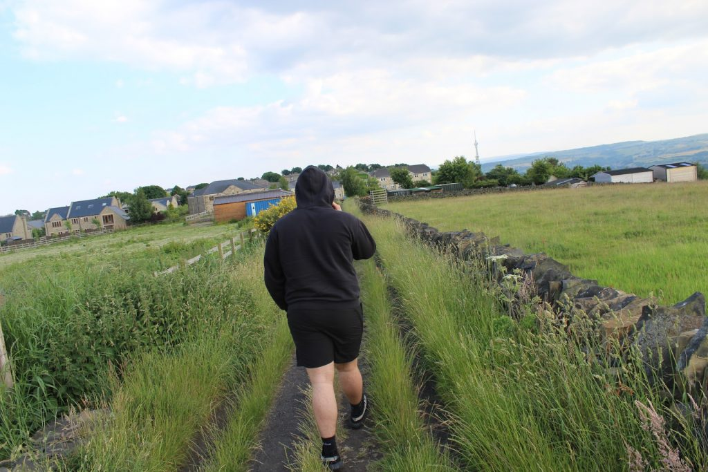 Josef Charlton - A man in black walking through a green field towards the sea