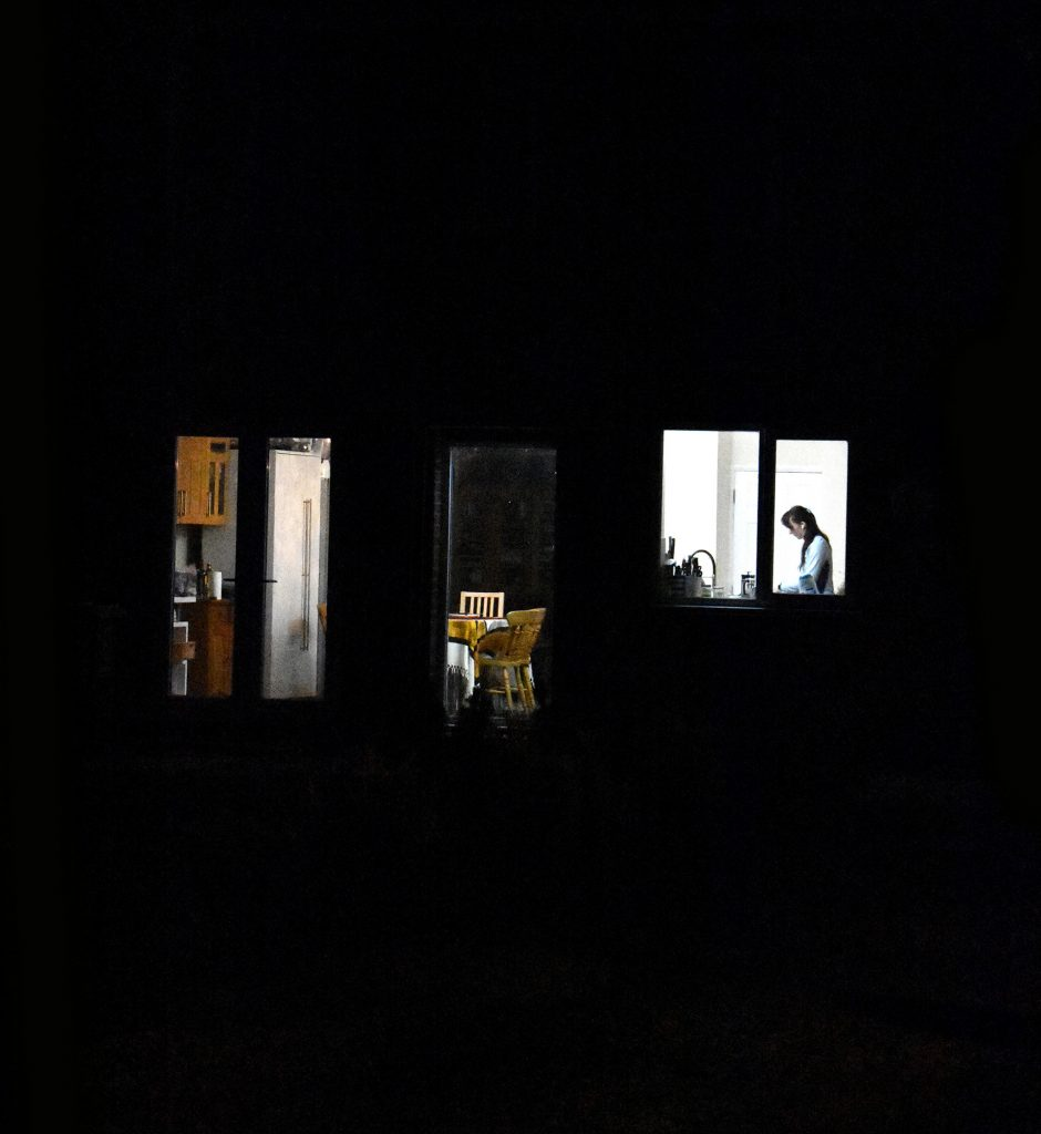 Lydia Sweasey - Three windows lit from the inside at night, showing sections of a kitchen and a woman cooking