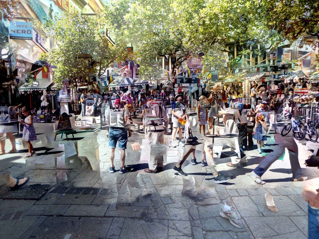Maisie Abbotts - A colourful market with green trees overhanging above and people walking in front