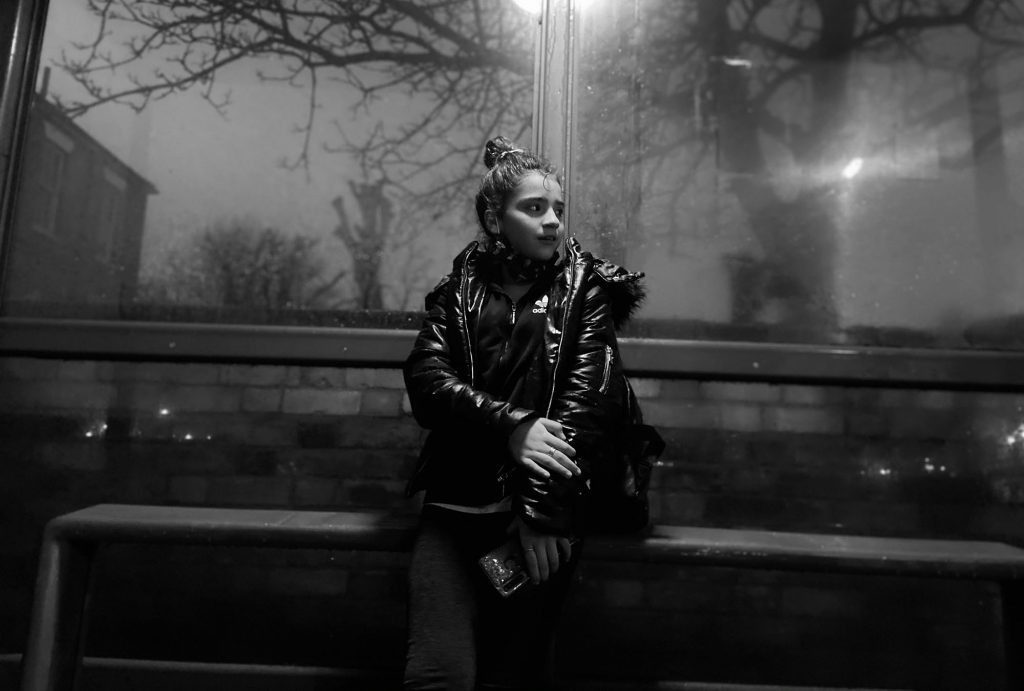 Megan Brookes - Black and white photo of a young woman stood in a bus shelter at night