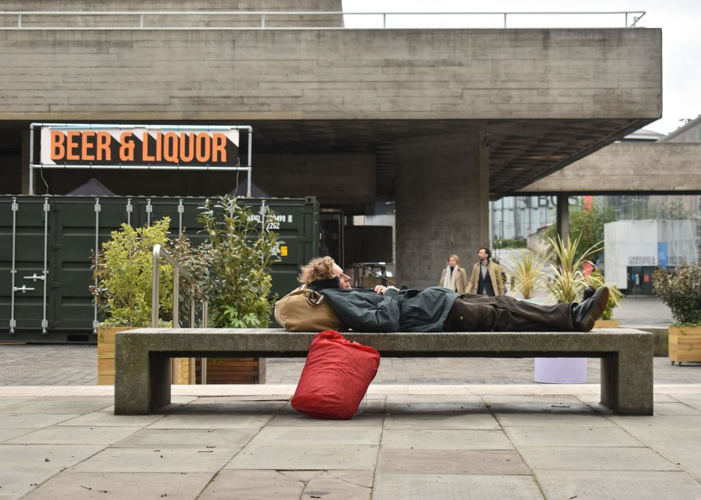 Miles Hewlett - A man sleeping on a concrete bench in a built up area with a sign reading Beer and Liquor