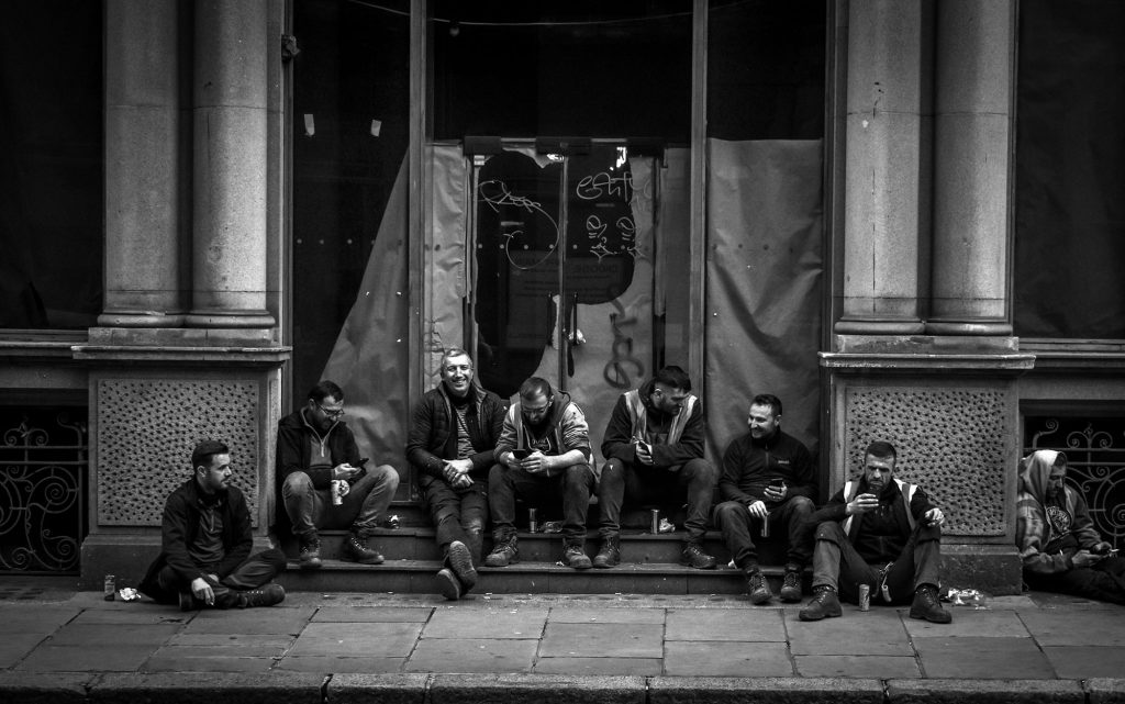 Miles Hewlett - Black and white photo of seven men sat on a doorstep outside a building