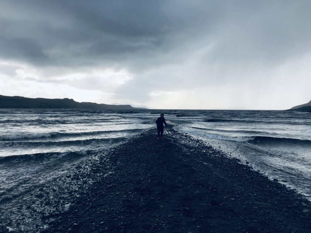 Niamh Melling - A silhouette of a figure at the end of a stretch of stones with sea on both sides