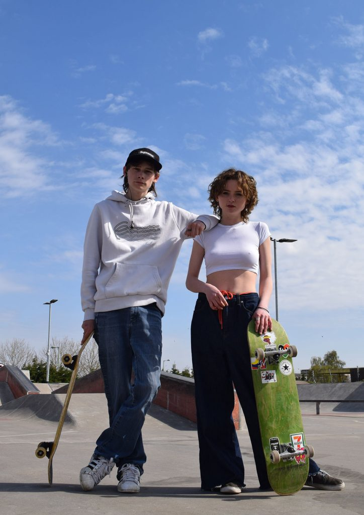 Sarayah Hayes - Two young people holding skateboards in a skate park looking at the camera