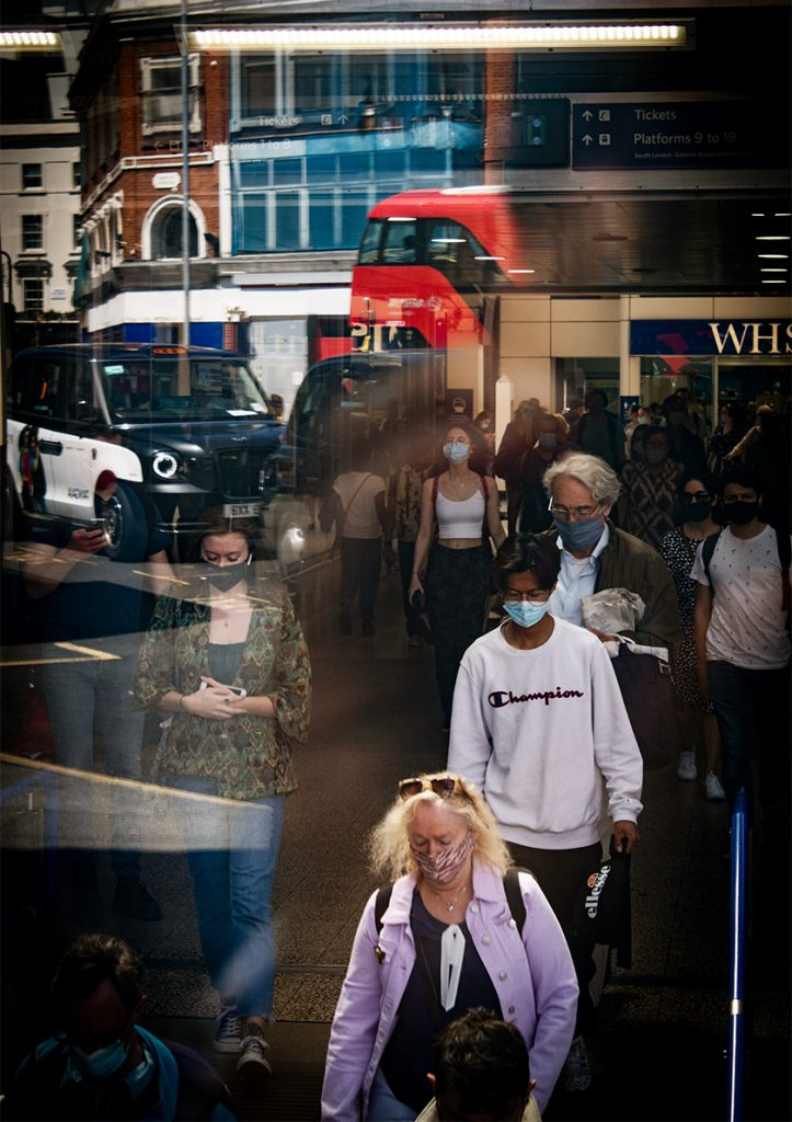 Simone Aldi - A busy street shown as a reflection, with people walking, a bus and a taxi