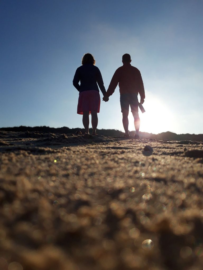 Sophie Markham - Two people holding hands silhouetted against the sun and walking on sand