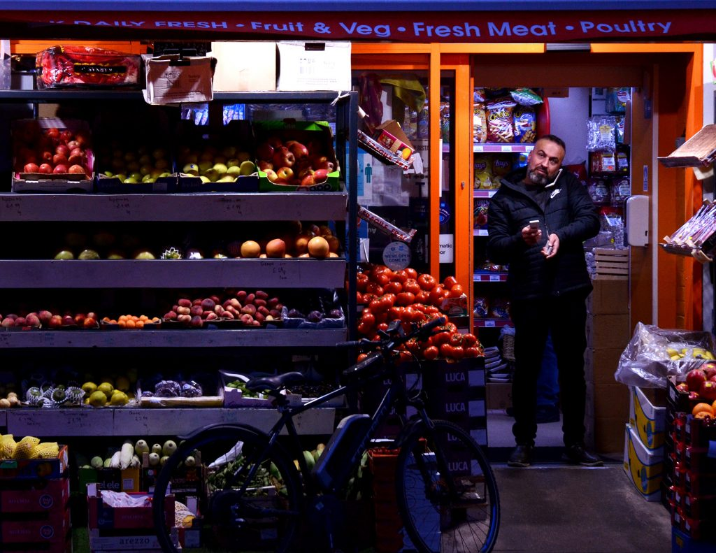 Thomas Gulley - A man stood in the doorway of a groceries shop with colourful pallets of fruit and vegetables covering the front of the shop