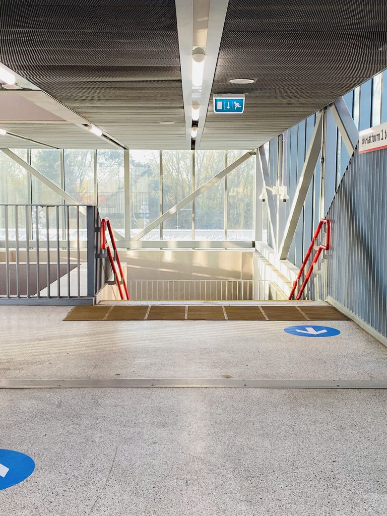 Daisy Buckle - Empty staircase in a train station with walls of windows and light pouring in